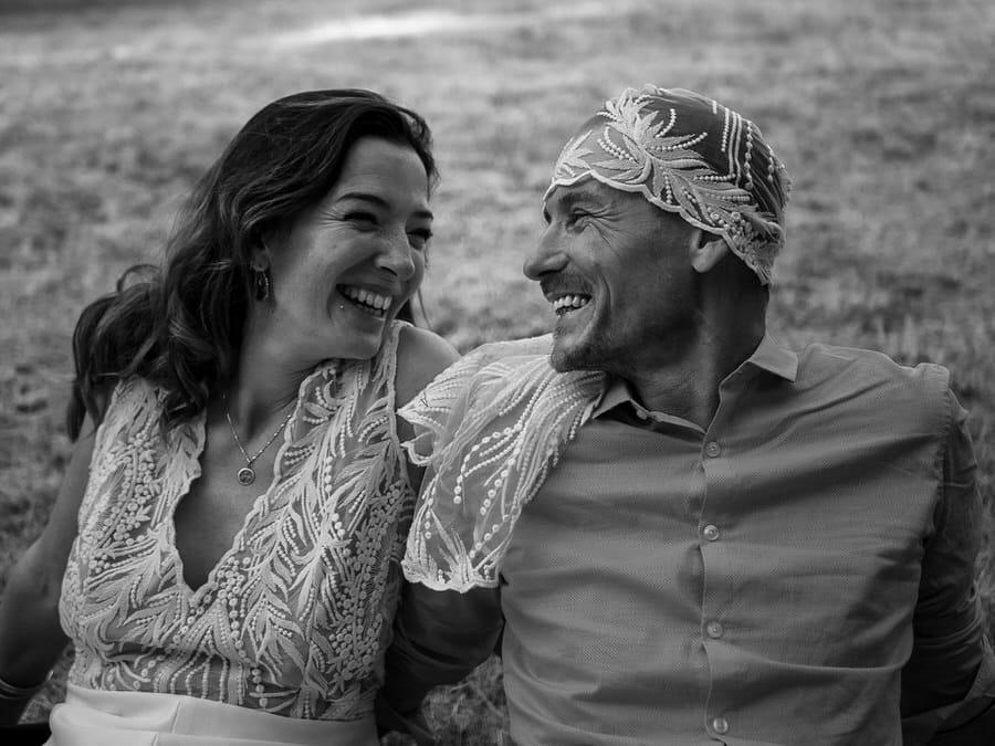 Une photographe de mariage à génissieux prend un couple qui rigole.