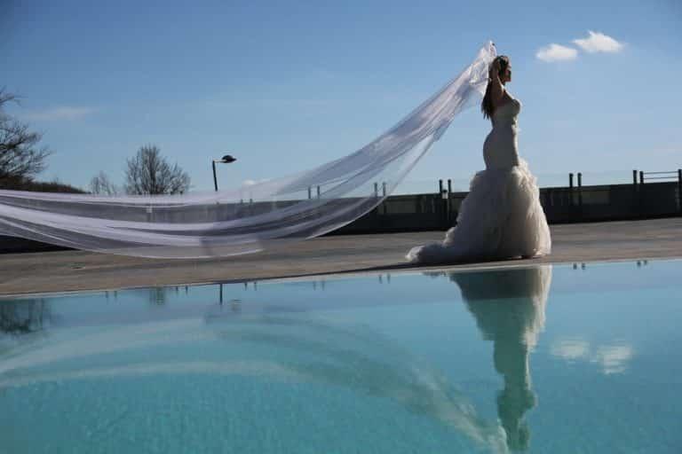 Un mariage piscine où la mariée laisse trainer sa robe de mariée au vent.