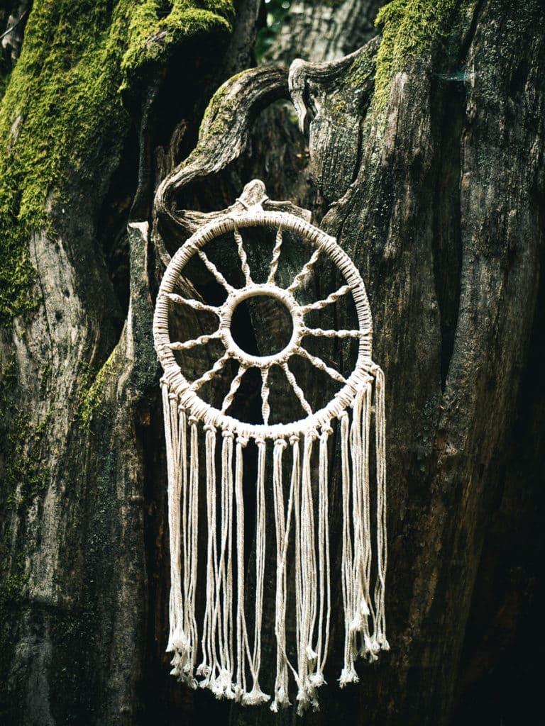 Une idée féérique pour un thème de mariage attrapes rêves. En voici un accroché à un arbre.